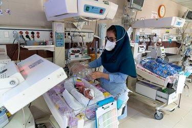 پرستار بخش مراقبت های ویژه نوزادان ( NICU 4 ) کلاهک اکسیژن را روی قفسه سینه و سر نوزاد قل چهارم ( قل D ) قرار می دهد.